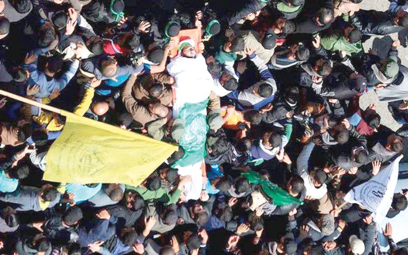 رايات الفصائل الفلسطينية توحّدت إلى جانب العلم الفلسطيني  في تشييع جثمان فقهاء.  الإمارات اليوم