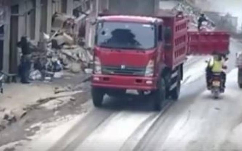 الصورة: بالفيديو.. باب شاحنة يصدم وجه سائق دراجة وزوجته